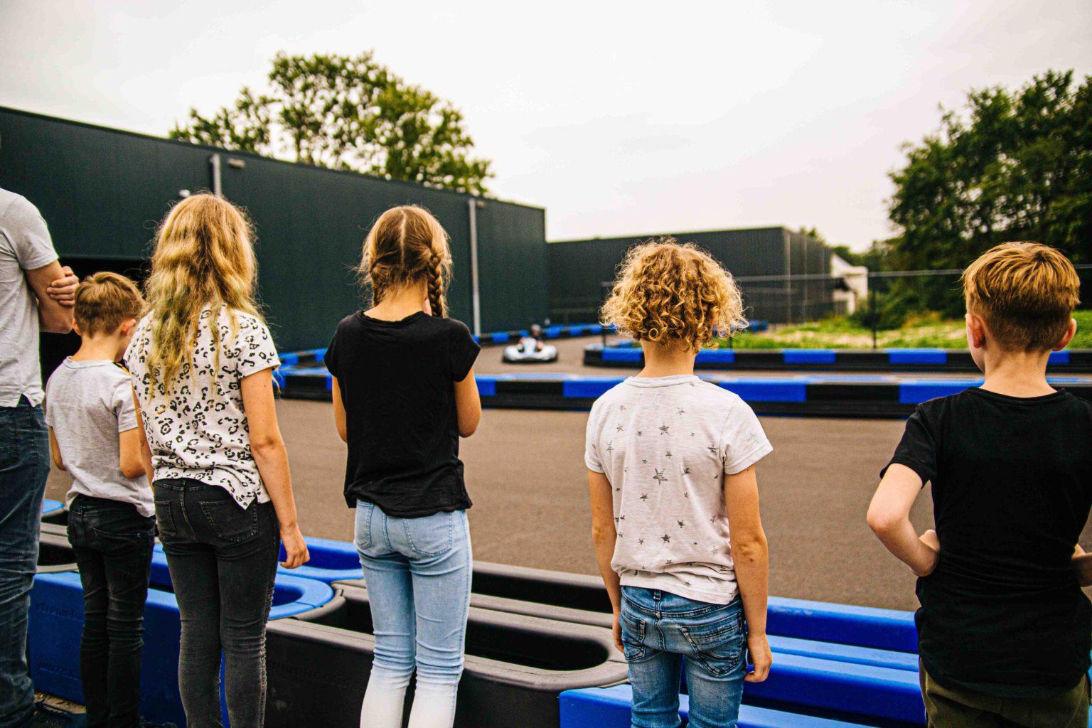 Kinderen kijken buiten naar de kartbaan van ZERO55 Apeldoorn